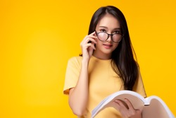 Young teacher woman wear eyeglasses holding book and looking at camera with confidence over yellow background, copy space. Beautiful girl get eyesight because she read a lot of books. She is genius