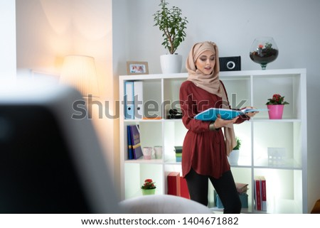 Young teacher. Young teacher wearing headscarf feeling involved in lesson preparation