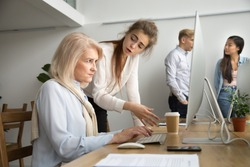 Young team leader correcting offended senior employee working on computer in office, female manager scolding aged old worker for mistake or incompetence, different generations and age discrimination