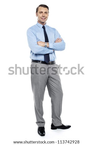 Young team leader smiling confidently with his arms crossed isolated against white. Full length shot