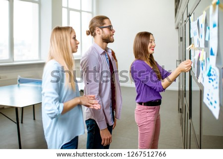 Young team of coworkers dressed casually talking together near the glass wall with some statistics and stickers in the office