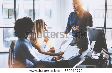 Young team of coworkers making great meeting discussion in modern coworking office.Hispanic businessman talking with two beautiful womans.Teamwork process.Horizontal,blurred background,flares effect #530012992