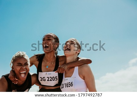 Young team of female athletes standing together and screaming in excitement. Diverse group of runners enjoying victory. Foto stock ©