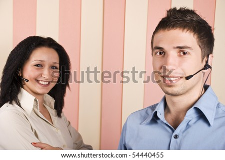 Young team with two people,woman and man customer service with headphone smiling and looking you,focus on man