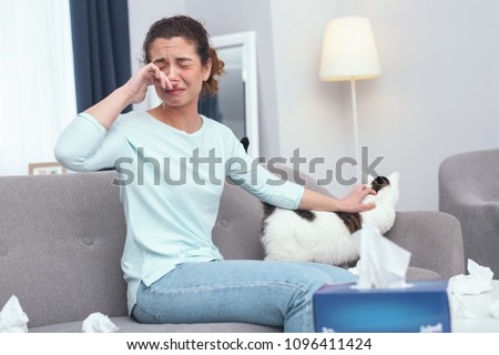 Young teary-eyed lady taking care of her cat suffering from first symptoms of feline fur allergy