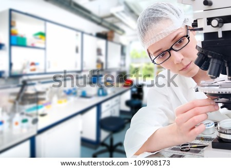 Young technical assistant tunes her microscope