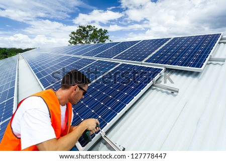 Young technician installing solar panels on factory roof #127778447