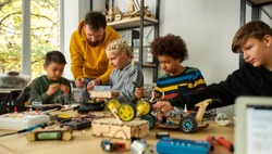 Young technicians building a robot, working with a wiring kit together with a male teacher at a stem robotics class. Inventions and creativity for kids. Selective focus. Web Banner