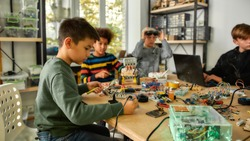 Young technicians building robots and vehicles, using soldering iron to join chips and wires, programming toys at stem robotics class. Inventions and creativity for kids