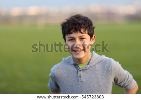 Young teen boy in the playing field during the golden hour - shallow depth of field - copy space left #545723803