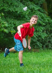 Young teen boy playing badminton in meadow with forest in background. Children with badminton rackets in hand. Friends have fun in summer park at day.