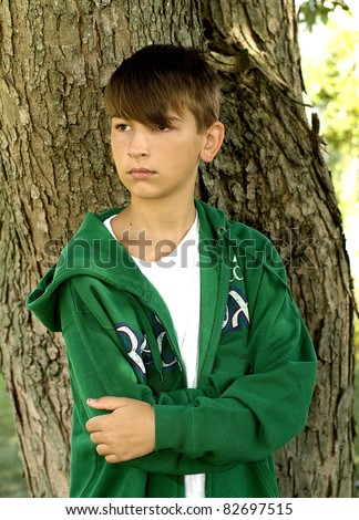 Young teen boy standing by tree in deep thought