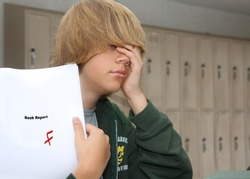 young teen boy with expression of despair upon finding a F grade on his paper.