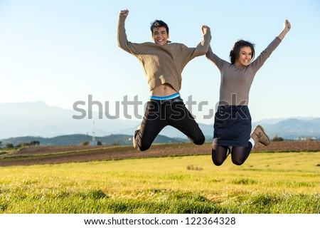 Young teen couple having fun jumping outdoors.