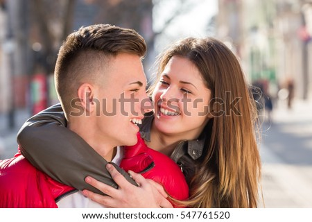 young teen couple having piggyback carrying on walking street in spring #547761520