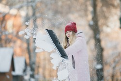 Young teen girl cleans snow near the house, holding a shovel and paddle spend time