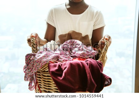 Young teen girl holding laundry basket