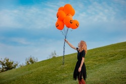 Young teen girl in black clothes holding bunch of halloween balloons on green hill. Copy space. Holiday concept.