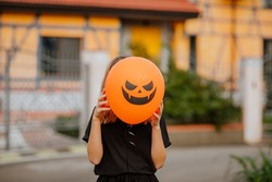 Young teen girl in black clothes standing against orange house and holding halloween balloon before her face . Holiday concept.