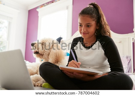 Young teen girl studying on her bed beside pet dog #787004602