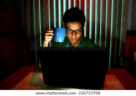 Young Teen holding a coffee mug in front of a laptop computer Photo of a Young Teen holding a coffee mug in front of a laptop computer