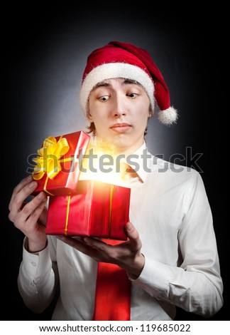 Young teen in Christmas hat opening red gift box with glowing light inside at black background
