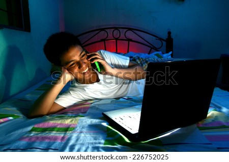 Young Teen in front of a laptop computer and on a bed and using a cellphone or smartphone Photo of a Young Teen in front of a laptop computer and on a bed and using a cellphone or smartphone