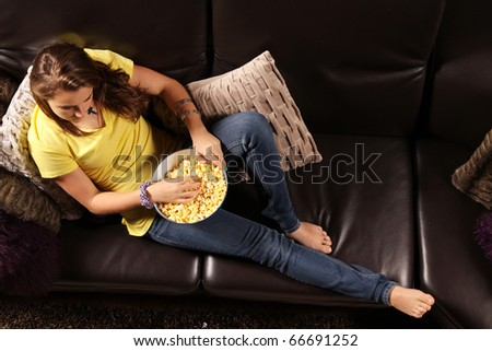 stock photo : Young teen laying down on a sofa with popcorn container ready ...