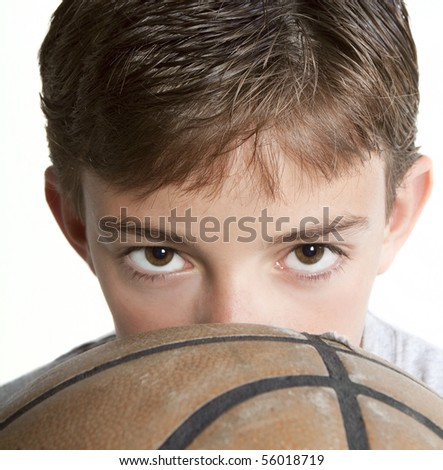 stock photo : Young teen peering over the top of a basketball.