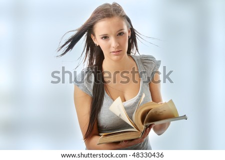 Young teen student woman reading a book.