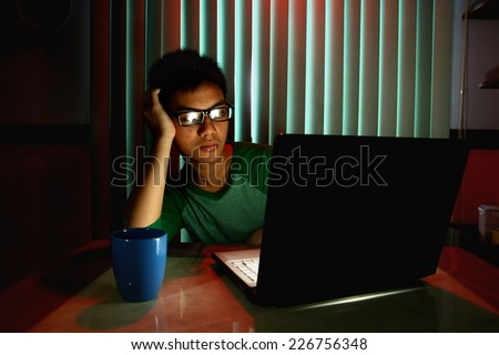 Young Teen with eyeglasses and bored in front of a laptop computer Photo of a Young Teen with eyeglasses and bored in front of a laptop computer