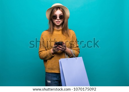 Young teen woman in sunglasses and hat looking something in smartphone and holding shopping bags in her hands feeling so happiness isolated on green background #1070175092