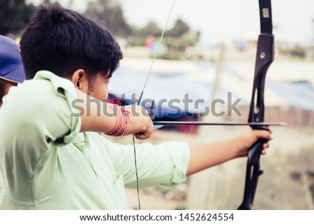 Young teenage boy aiming at target and training to shoot using bow and arrow sport #1452624554