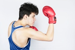 Young teenage boy boxing on light background. A teenager in boxing gloves trains a kick from below - an uppercut. A boy has a focused look, side view