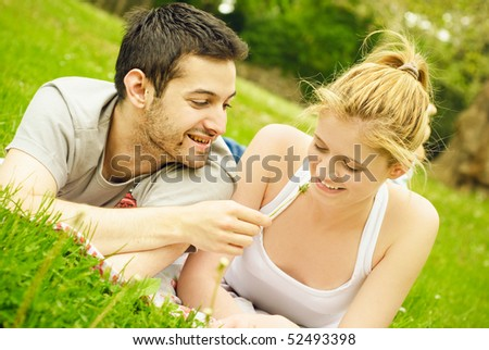 Young teenage couple lying on a grass
