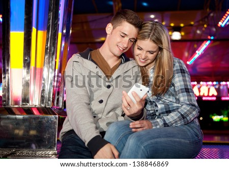 Young teenage couple sitting near a funfair attraction ride with colorful lights, using a smartphone during a fun night out.