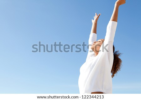 Young teenage girl breathing fresh air with her arms outstretched up and relaxing while standing against a blue sky.