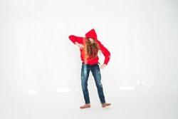 Young teenage girl dancing in full growth on white background in studio in rays of the sun. Rejoices and indulges. Good mood concept. Lifestyle photo