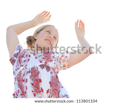 Young teenage girl dancing with her arms up against a sunny sky. - stock photo