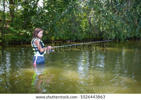 Young teenage girl fishing in the water with rod