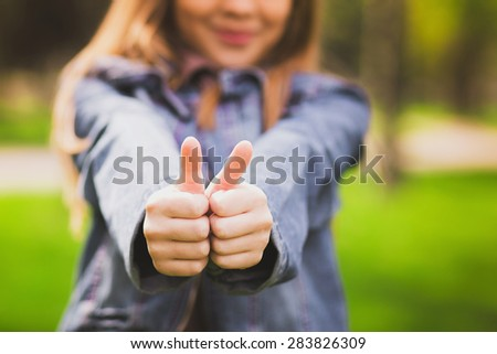 Young teenage girl giving thumb up as sign of success. Portrait of happy smiling anonymous caucasian child dressed in blue jeans casual clothing. Focus at hands. #283826309