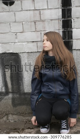Young teenage girl near a wall with graffiti. Outdoors #309776285