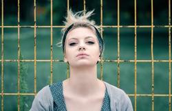 Young teenage girl posing on fence