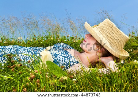 Young teenage girl resting on summer meadow in straw hat