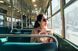 Young teenage girl using her cell phone in public transportation while commuting. asian woman in sunglasses looking view outside the bus window. empty streetcar cable car in san francisco.