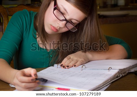 Young teenage girl with glasses doing homework