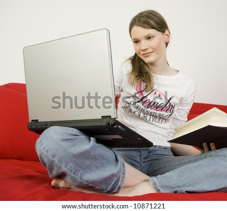 Young teenage girl working with laptop and book.