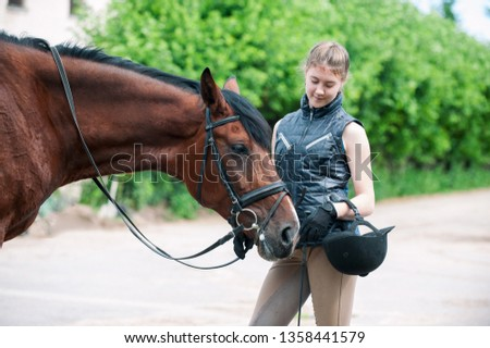 Young teenage lady leads and tenderly looking at her favorite red horse. Vibrant colored outdoors horizontal summertime image. #1358441579