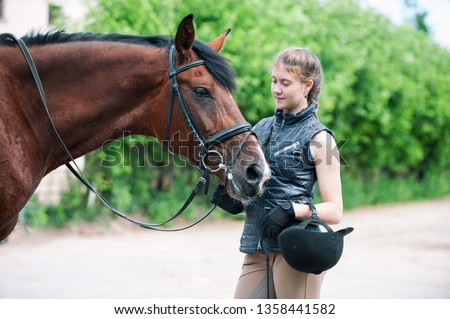 Young teenage lady leads and tenderly looking at her favorite red horse. Vibrant colored outdoors horizontal summertime image. #1358441582
