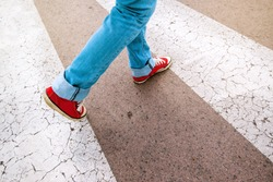 Young teenage person wearing blue jeans and red sneakers, walking over pedestrian zebra crosswalk, selective focus